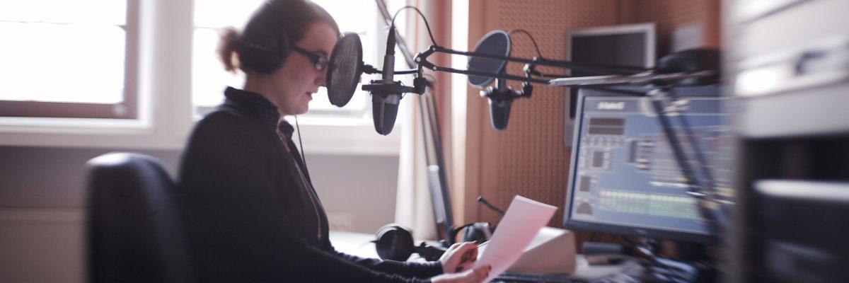 Frau in einem Radiostudio liest Text in ein Mikrofon.